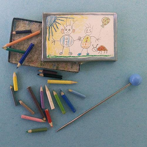 Miniatuur kleurpotloden in doos met tekening op deksel