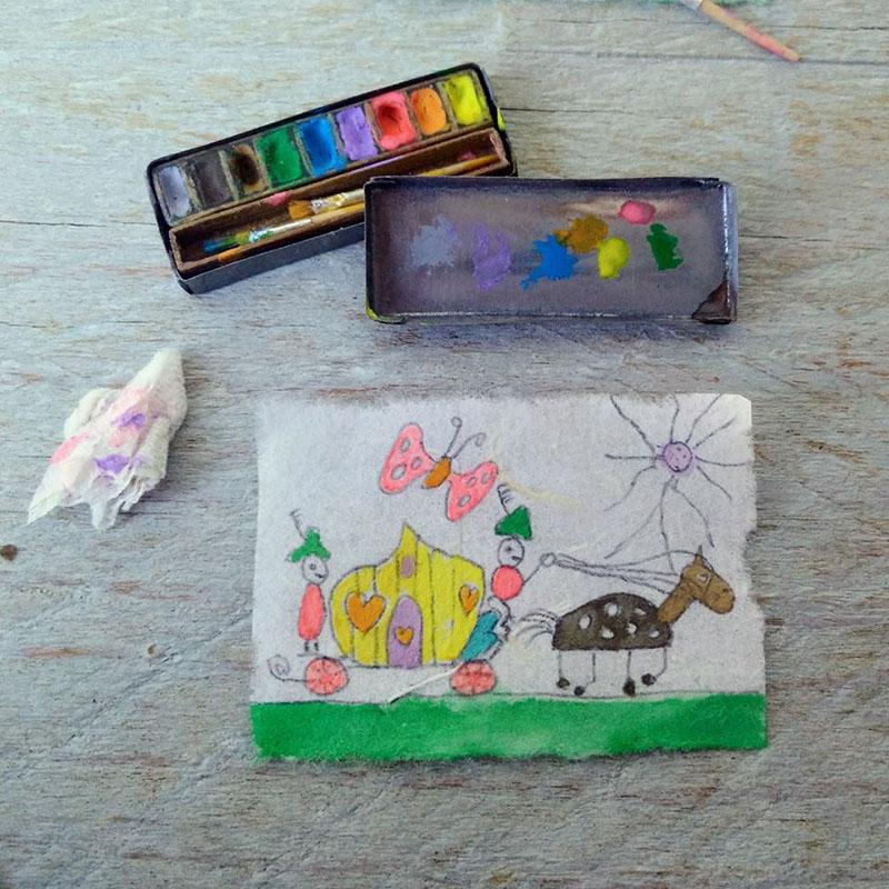 Een prachtig miniatuur aquarelverfdoosje met penseeltjes en een kindertekening.