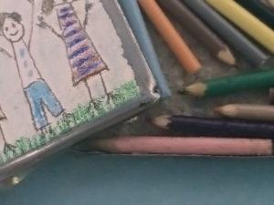 Een miniatuur kleurpotlodendoosje met een kindertekening op de deksel. Leuk detail: sommige kleurpotloodjes zijn aan het eind 'ingebeten'.